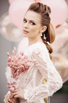 Colpo in testa di una splendida donna bruna con una pelle impeccabile, un'acconciatura alta, un trucco professionale e un mazzo di fiori rosa che guarda l'obbiettivo. sfondo rosa sfocato.
