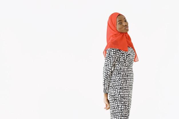 Colpo in testa di una donna musulmana religiosa soddisfatta adorabile con un sorriso gentile, pelle scura e sana, indossa una sciarpa sulla testa. isolato su sfondo bianco.