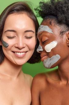 Colpo in testa di donne multietniche con pelle ben curata applicare crema nutriente e maschere sorridono piacevolmente stare vicine l'una all'altra hanno gli occhi chiusi