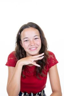 Ritratto di colpo in testa delle mani emozionanti della ragazza sul mento che posa nello studio