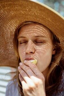 Colpo in testa di donna in cappello estivo di paglia che mangia verdure grigliate all'aperto, con gli occhi chiusi. motivo di luci e ombre sul viso