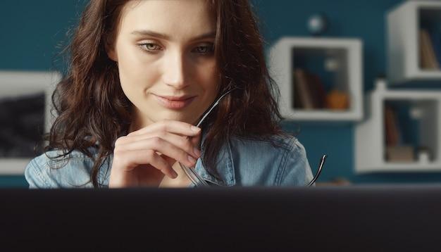 Headshot di giovane donna allegra tenendo gli occhiali guardando lo schermo del computer, vista frontale