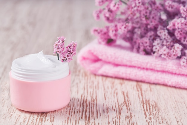 Crema cosmetica curativa a base di erbe, prodotto igienico per la cura della pelle o maschera per il trucco rilassante in un barattolo rosa con un asciugamano su un tavolo di legno.