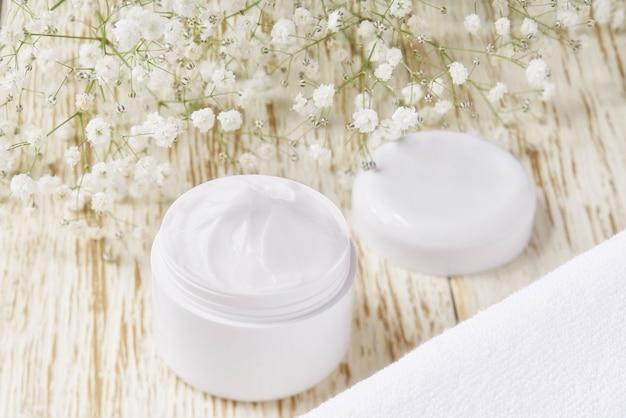 Crema cosmetica curativa a base di erbe, prodotto igienico per la cura della pelle o maschera per il trucco rilassante in un barattolo di plastica con un asciugamano su un tavolo di legno.