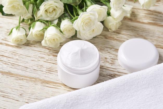 Crema cosmetica curativa a base di erbe, prodotto igienico per la cura della pelle o maschera per il trucco rilassante in un barattolo bianco con un asciugamano su un tavolo di legno.