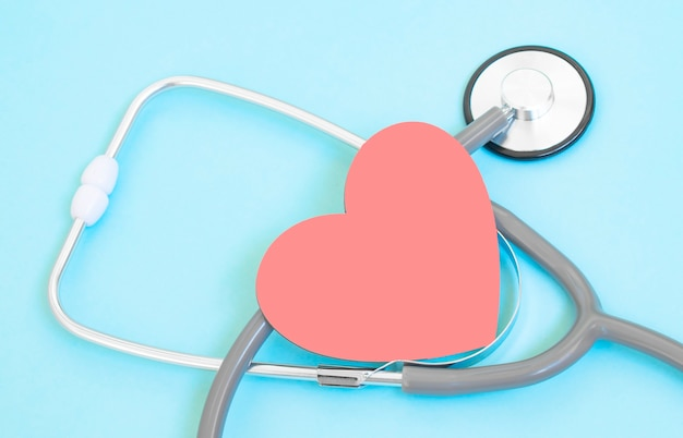 Check-up sanitario con cuore rosso e stetoscopio su sfondo blu. guarigione concetto di cura e copia dello spazio. sopra la vista delle apparecchiature mediche per il trattamento delle malattie sullo sfondo blu.