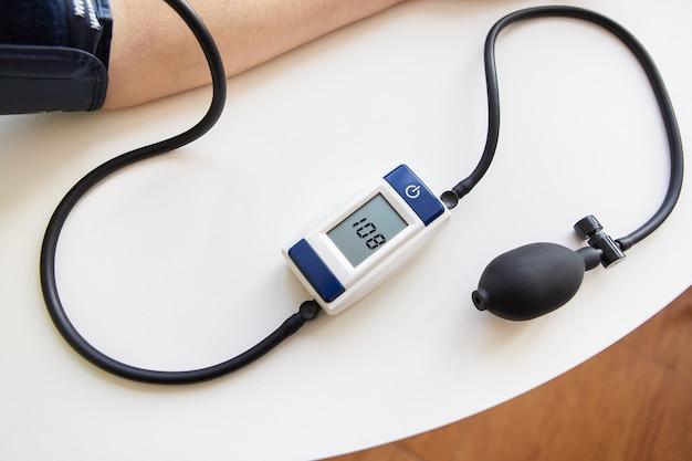 Concetto di salute e cura. misurazione della pressione sanguigna. la donna misura la pressione sanguigna. autodiagnosi a casa. vista dall'alto.