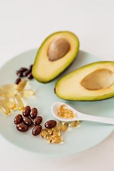 Assistenza sanitaria e concetto di dieta. avocado e olio di pesce in capsule per vitamina d e acidi grassi omega-3 in un piatto su sfondo bianco