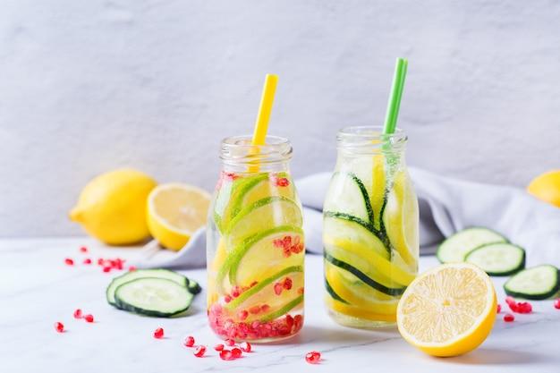 Assistenza sanitaria, fitness, concetto di dieta sana alimentazione. fresco fresco limone cetriolo rosmarino melograno acqua infusa, bevanda disintossicante, limonata in un barattolo di vetro per le giornate primaverili estive.