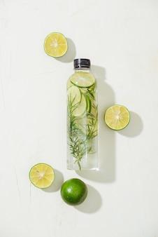 Assistenza sanitaria, fitness, concetto di dieta sana alimentazione. acqua fresca infusa di rosmarino al limone, cocktail, bevanda disintossicante, limonata in un barattolo di vetro. sfondo piatto disteso con vista dall'alto chiaro