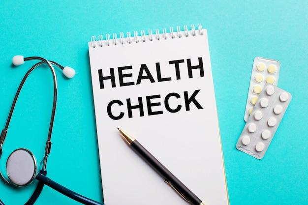 Controllo di salute scritto in un blocco note bianco vicino a uno stetoscopio, penne e pillole su una superficie azzurra