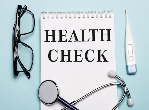 Controllo di salute scritto su un blocco note bianco accanto a uno stetoscopio, occhiali e un termometro elettronico su sfondo azzurro