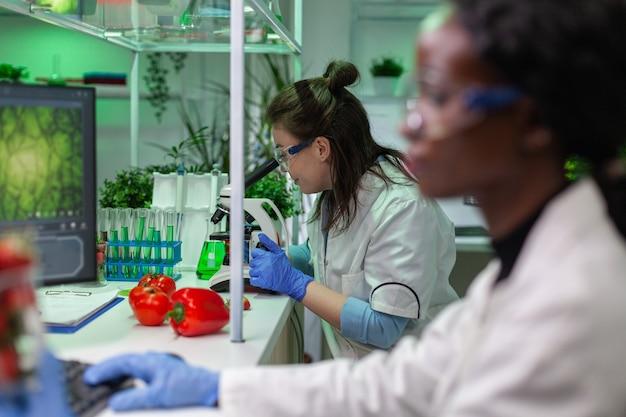 Chimico sanitario che controlla un campione di carne vegana guardando al microscopio