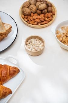 Colazione salutare e colorata: cialde, muffin, mandorle, nocciole, frutta fresca varia sul tavolo. concetto di salute alimentare. vista dall'alto.
