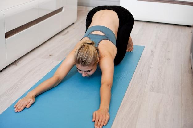 Concetto di salute. donna che medita o che fa esercizio di yoga a casa