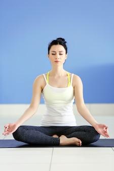 Concetto di salute. la giovane donna attraente fa esercizio di yoga nella stanza contro il muro blu