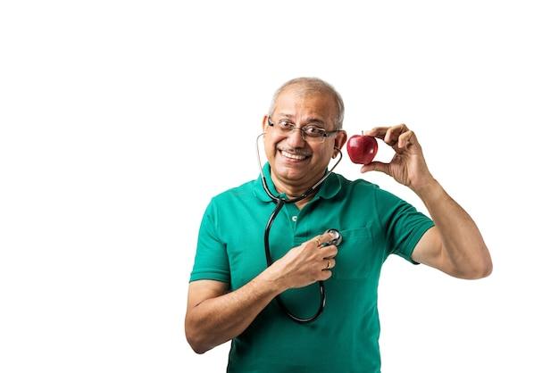 Consapevole della salute indiano asiatico senior maschio adulto controllando i battiti cardiaci con lo stetoscopio, tenendo il cuore del giocattolo o la mela in altra mano, mostrando segno ok