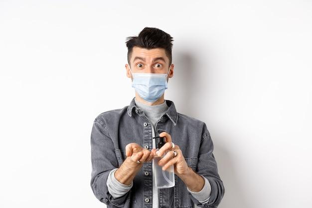 Concetto di salute, covid e pandemia. ragazzo moderno in maschera per il viso mani pulite con antisettico, utilizzando la bottiglia di disinfettante, in piedi su sfondo bianco.