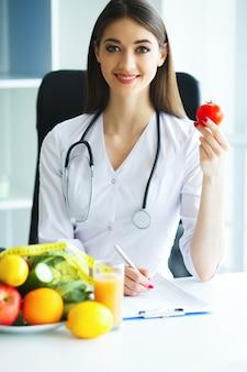 Salute. il medico firma un programma dietetico. il dietista tiene nelle manciate di pomodoro fresco. frutta e verdura.