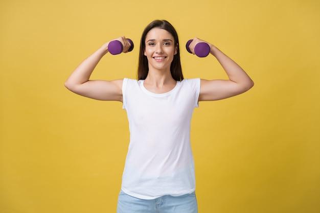 Concetto di salute e fitness: scatto di una giovane donna bella e sportiva che solleva pesi su sfondo giallo.