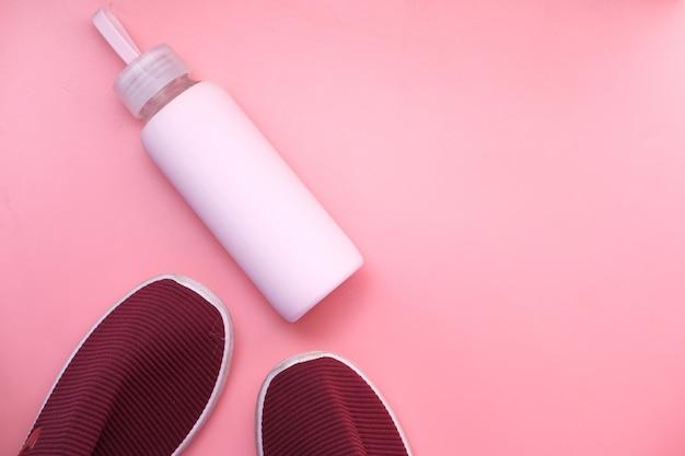 Concetto di salute e fitness con scarpa e bottiglia d'acqua su sfondo rosa