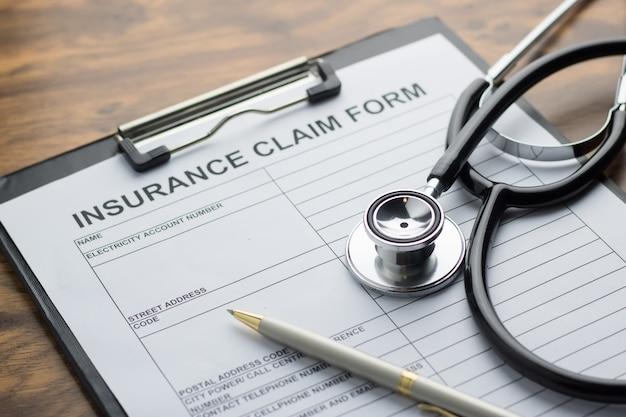 Modulo di reclamo dell'assicurazione malattia con lo stetoscopio sul fuoco selettivo della tavola di legno
