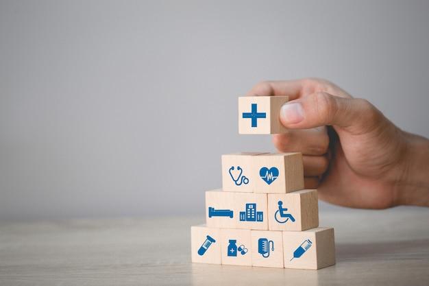 Concetto di assicurazione sanitaria, mano che organizza l'impilamento del blocco di legno con l'icona sanitaria medica