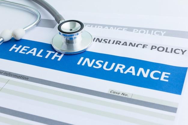 Modulo di assicurazione sanitaria con stetoscopio in vista dall'alto