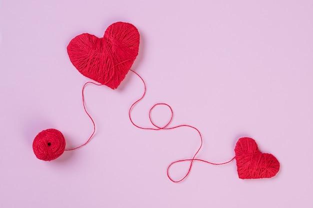Salute, medicina, concetto di cardiologia. cuore rosso. problemi con il cuore. il cuore e il cardiogramma sono fatti di filo rosso. battito cardiaco, sentimenti, amore, concetto di romanticismo. copia spazio