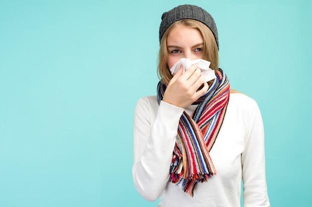 Concetto di medicina e salute - ragazza teenager triste che soffia il naso nel tessuto