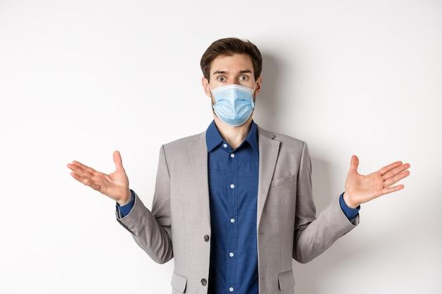 Salute, pandemia e concetto di business. uomo d'affari confuso in maschera medica e tuta allarga le mani lateralmente e guarda perplesso, non riesco a capire, sfondo bianco.