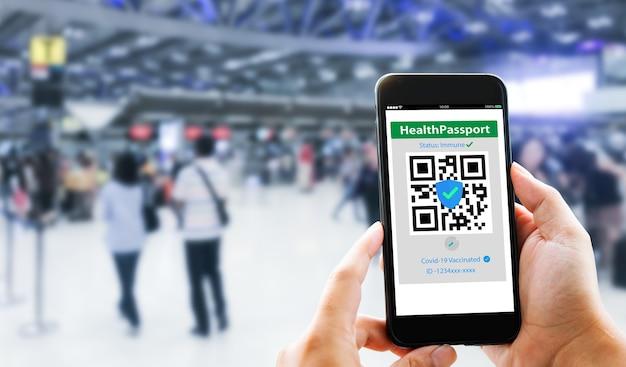 Passaporto sanitario covid19 conceptle mani del viaggiatore mostrano il passaporto sanitario covid19 con aeroporto sfocato