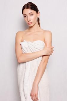 Concetto di salute, persone e bellezza - bella donna in accappatoio bianco dopo la spa. foto di donna ben curata su sfondo bianco. concetto di benessere e spa.