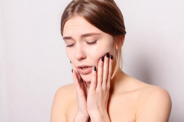Concetto di salute, persone, denti e stile di vita - problema dei denti. donna che sente dolore al dente. primo piano di bella ragazza triste che soffre di forte dolore ai denti. attraente donna sensazione di mal di denti doloroso