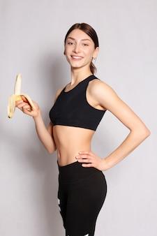 Concetto di salute, persone, cibo, sport e bellezza - giovane ragazza sportiva che tiene in mano un grappolo di banane. cibo sano e dieta. il concetto di corretta alimentazione. cura del corpo. su uno sfondo grigio