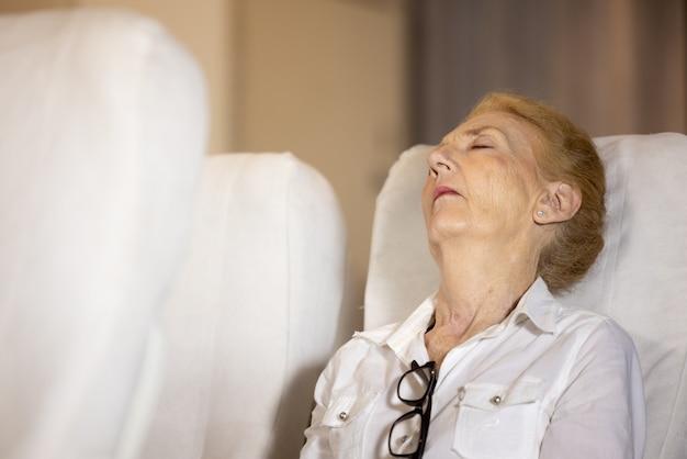 Problema di salute su un aereo, la donna anziana passeggero sull'aereo ha sentito dolore alla spalla da un lungo viaggio in aereo