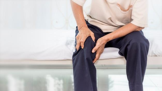 Concetto di problema di salute; vecchia donna che soffre di dolori al ginocchio a casa.