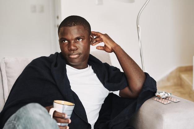 Problemi di salute uomo africano con le pillole sul divano.