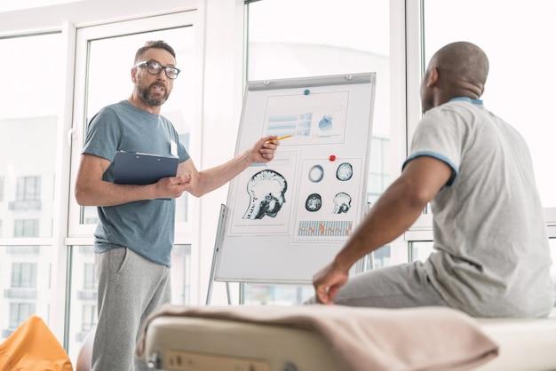 Problemi di salute. terapista professionista intelligente che guarda il suo paziente mentre gli parla dei suoi problemi di salute