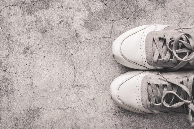 Concetto di salute e sport. vista dall'alto di scarpe da ginnastica grigie su un tavolo di cemento con spazio di copia