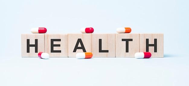 Parola di salute fatta su blocchi di cubi di legno e fiori in una pentola sullo sfondo.