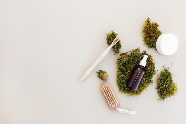 Il concetto di assistenza sanitaria di accessori da bagno flay giaceva con una bottiglia di olio essenziale, spazzolino da denti in legno, spazzola per i piedi, sapone e muschio verde come rifiuti zero eco, concetto di ambiente privo di plastica