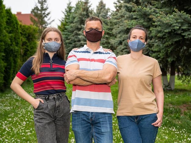 Concetto di assistenza sanitaria. famiglia in maschere protettive in posa nel parco