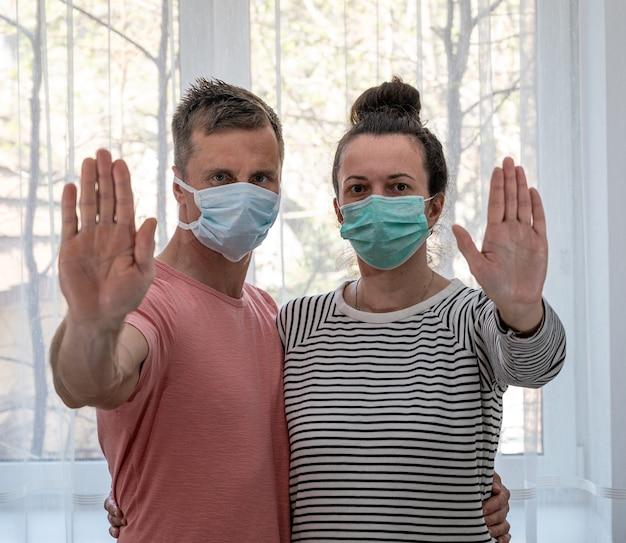 Concetto di assistenza sanitaria. coppia triste in maschere in posa vicino alla finestra a casa