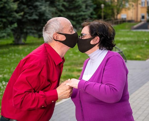 Concetto di assistenza sanitaria. coppia senior in maschere facciali protettive baciare nel parco