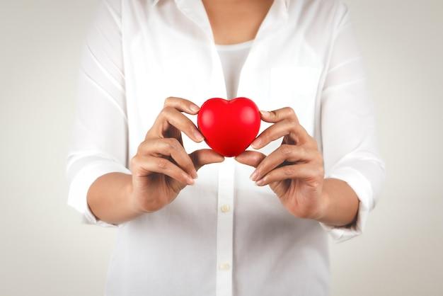 Concetto di sanità della mano della giovane donna che tiene cuore rosso