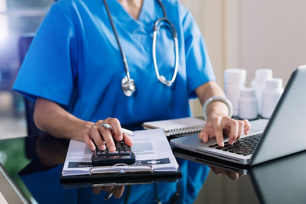 Costi sanitari e concetto di tasse.la mano del medico intelligente ha utilizzato una calcolatrice e uno smartphone, tablet per le spese mediche in ospedale nella luce del mattino