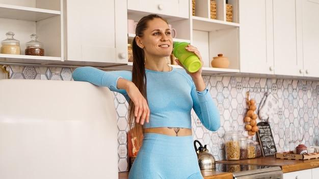 Concetto di assistenza sanitaria e dieta. la bella donna beve l'acqua da una bottiglia di sport dopo un allenamento a casa. è in cucina vicino al frigorifero.
