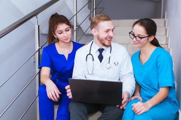 Assistenza sanitaria. un gruppo di studenti di medicina comunica davanti a un laptop. discussione della diagnosi.