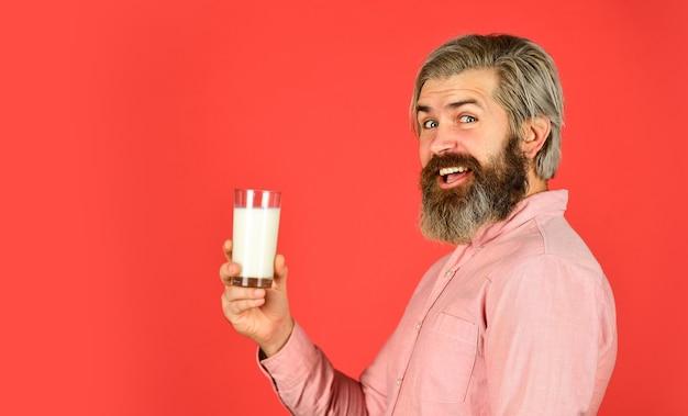 Concetto di supporto sanitario e immunitario. menù colazione a base di latte. felice contadino presente bicchiere di latte. l'uomo barbuto beve latte utile. esercizio e concetto di stile di vita. copia spazio.